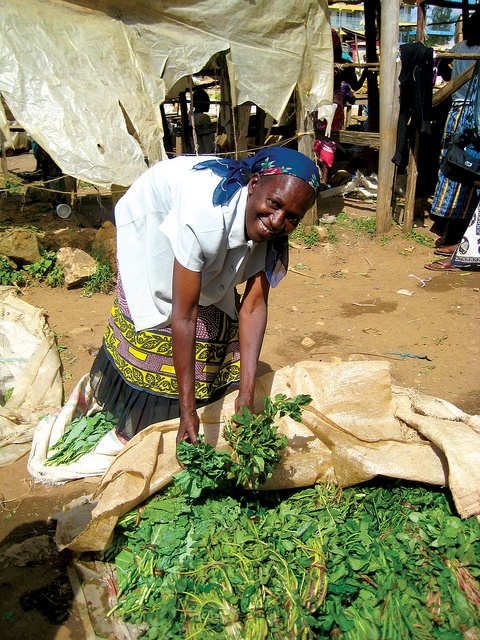 During a UUSC service-learning trip to Kenya, a member of the Kenya National Alliance of Street Vendors and Informal Traders (KENASVIT) displays the vegetables that she sells in the market, March 2009.