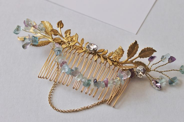 Bohemian Gold Tone Brass leaf and gemstone branch hair comb - Made to order please allow 4 weeks for production + shipping.This lovely brass leaf and gemstone (fluorite) hair comb looks beautiful at the back of a braided up do.Perfect for a Bohemian wedding or for a special event. This piece features numerous brass leaf stampings hand-wired onto a gold-plated comb. The fluorite chips are hand-wired into branches and flow perfectly with the brass branches. Fluorite gemstones and gold chain…