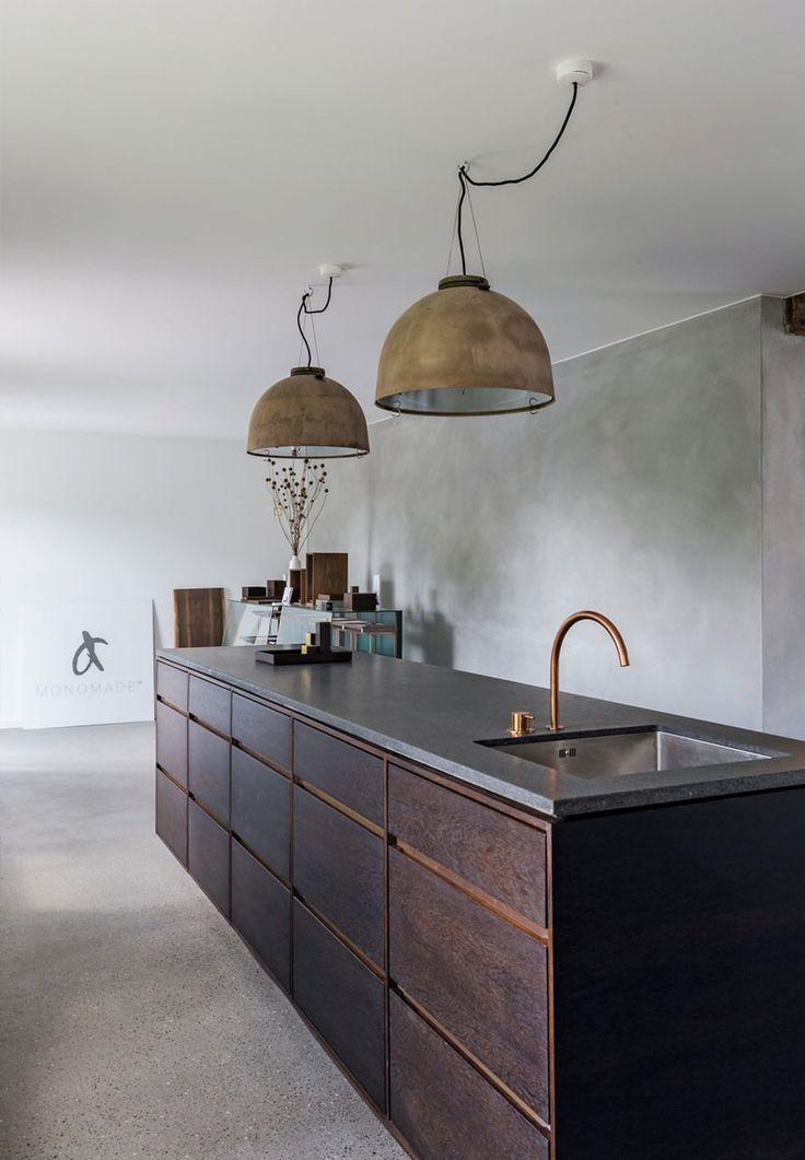Stylish kitchen design in dark wood with industrial pendants.