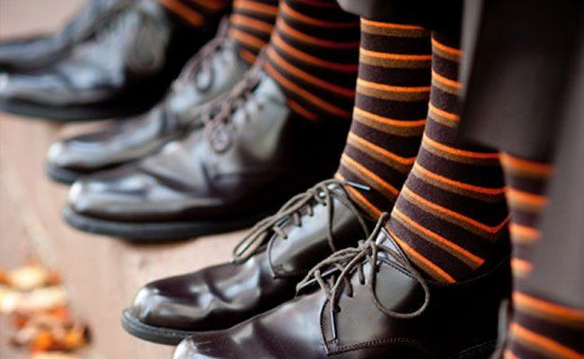 Orange and black stripes socks make a perfect addition to the groomsmen outfits for a Halloween wedding #wedding #halloween