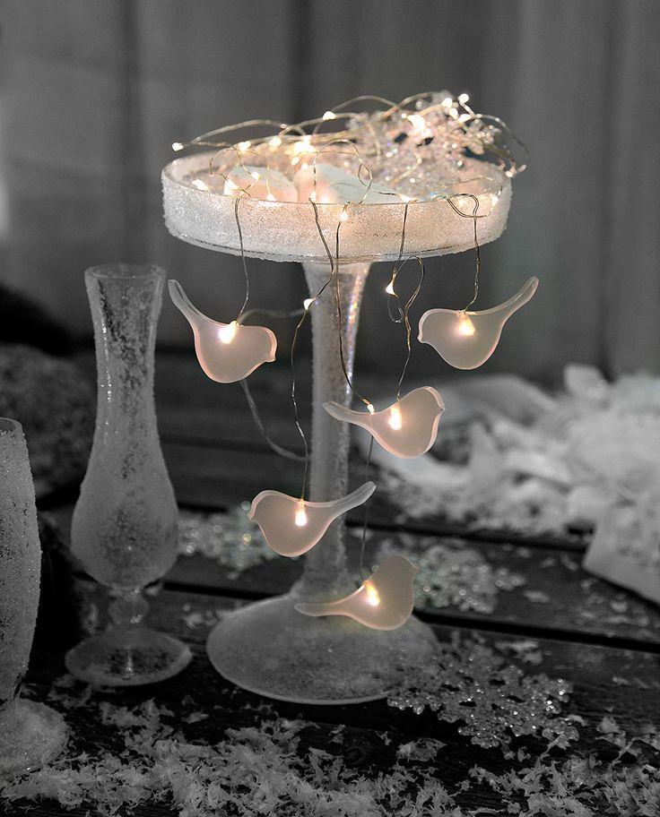 String er en vakker slynge med 46 varmhvite LED lys og små, søte fugler i akryl. Den er satt sammen av flere tråder i en bukett av lys, tre lengder med 10 lys og 2 lengder med 8 lys. Bruk den til å dekorere bordet til fest eller til å pynte opp elementer som vakre skåler eller blomster rundt i huset.