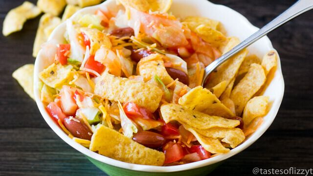This vegetarian Frito Taco Salad comes together quickly. It's full of tomatoes, onions, cheese, lettuce and beans and has crunchy Fritos mixed in!