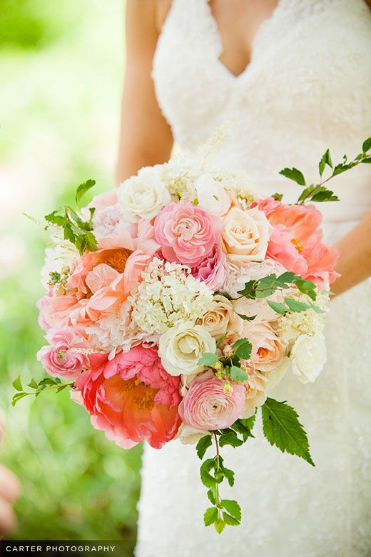 Bridal bouquet featuring coral charm peonies, ranunculus, lacey hydrangea, garden roses, sahara roses, astilbe, and stock