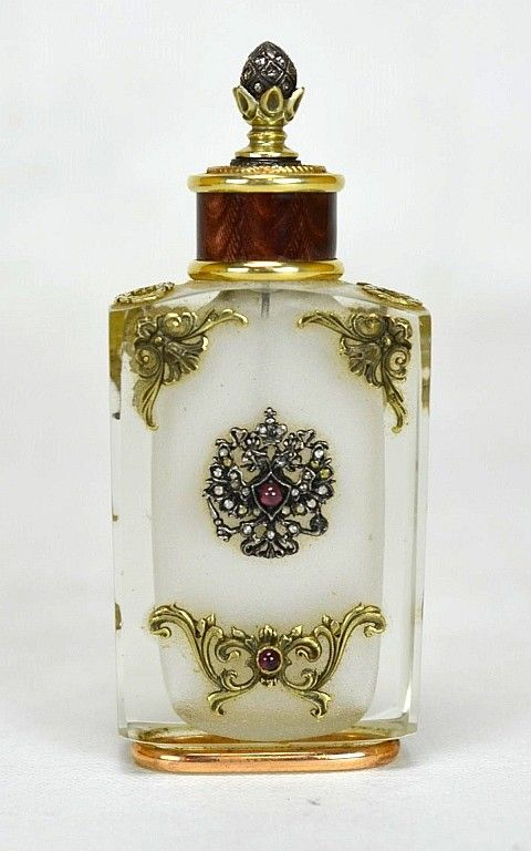"Karl Gustaf Hjalmar Armfeldt (1873 - 1959) Faberge perfume bottle. Adorned with gold scrolling decoration as well as diamonds and rubies. Marked with the Faberge mark ""56"" ""?A"", stopper is marked with the # ""88"". ARMFELDT, Karl Gustaf Hjalmar"