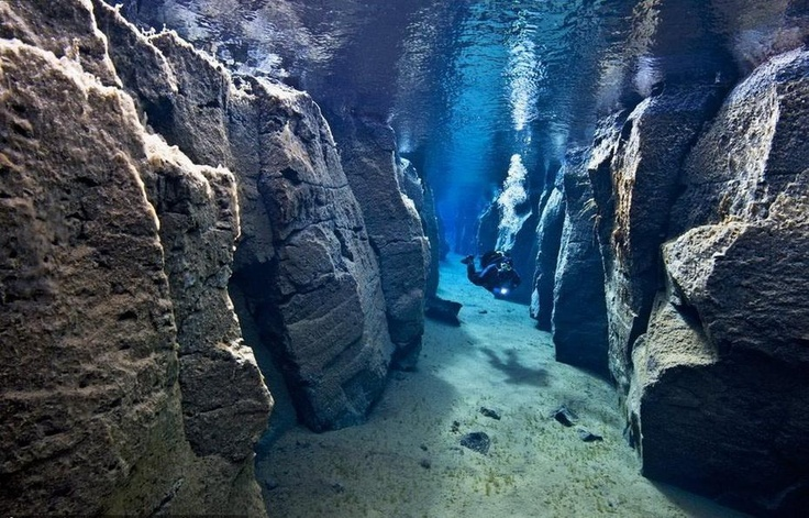 Scuba diver between two tectonic plates - the American and the Eurasian. Picture is taken near Iceland. Parts of the gap are on land or only slightly below the surface.  By the way, have you read our article about scuba myths: http://www.dive.in/articles/diving-myths-debunked/