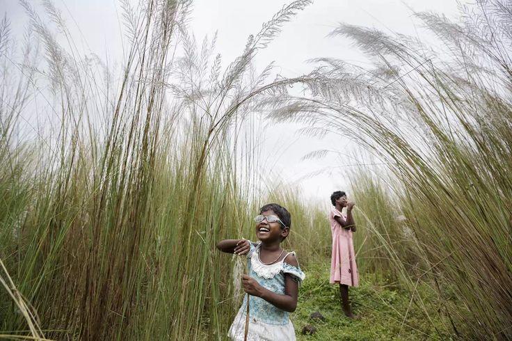 """《初见光明2》。12岁的盲女索妮和5岁的盲女安妮塔·辛格生在贫苦的家庭,患有先天性白内障症。她们单独活动不安全,所以父母得随时陪伴。治疗这种疾病的手术其实很简单,只需要15分钟的时间,但这个家庭极为贫困,没有能力做去必要的手术。印度有1200万盲人,其中绝大部分为白内障致盲。数百万人遭受这种疾病的折磨,贫困是主要原因。最近,人们捐助的资金让这对姐妹有幸接受了手术治疗。这张照片是有关文章的一部分,文章描写她们在接受复明手术之前、手术期间以及手术后重见光明的生活故事。专业赛""""时政""""栏目入选作品,作者:南非Brent Stirton。"""