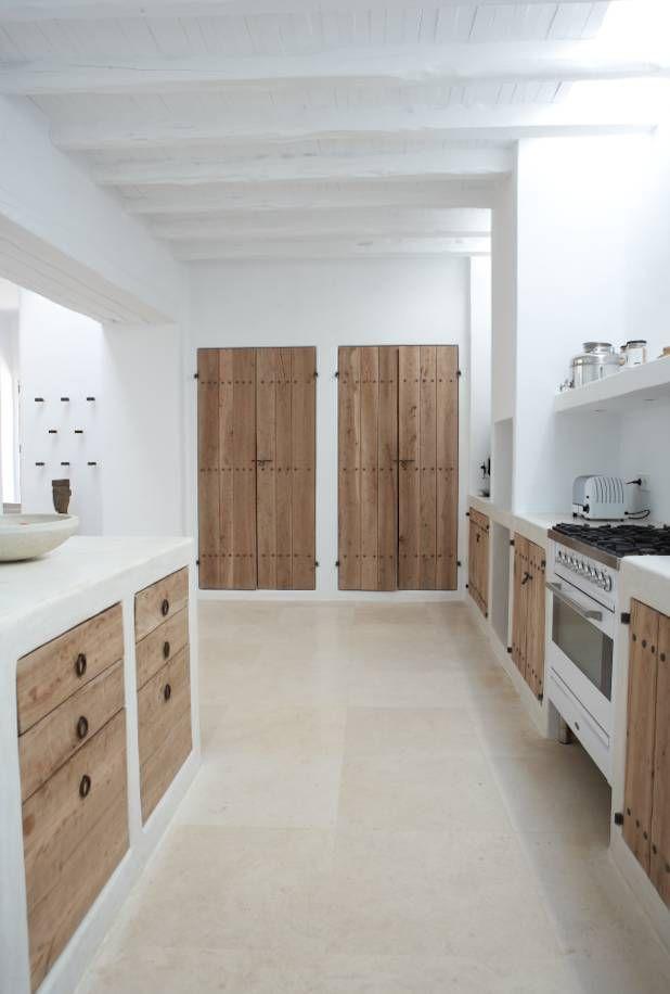 Une cuisine toute blanche, aux éléments de placards et portes en bois naturel. Grand carrelage beige au sol. Clarté et épure.