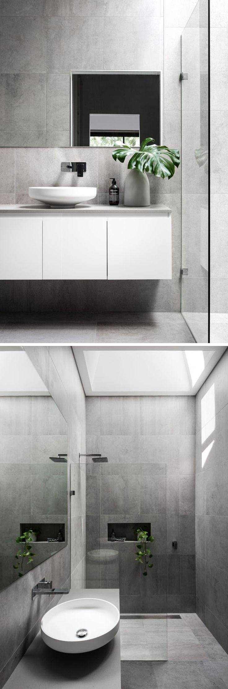 Этот современный мастер ванная комната имеет большой серый плиток, покрывающих стены и пол. Стеклянная перегородка отделяет душ от белой плавающей суета, и просвет добавляет большое количество естественного света в комнату.