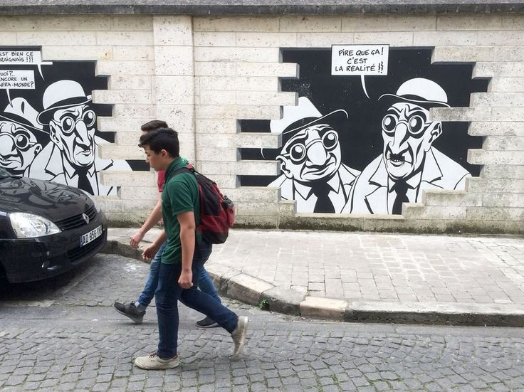 """Pedestrians walking down Rue de Beaulieu will notice a conspicuous sequence of six panels painted on a brick wall: Marc-Antoine Mathieu's Realite, Sortie de Secours (Reality, Emergency Exit), produced in 1999. Through the technique of trompe l'oeil, the bricks of the wall are gradually removed to reveal Mathieu's character, Julius Corentin Acquefacques, an official in the so-called Ministry of Humor whose last name is a phonetic reversal of """"Kafka."""" With him is a caricature of Jean…"""