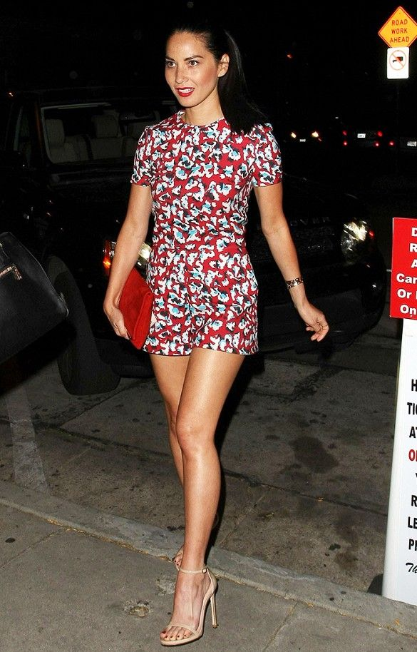 Olivia Munn wears a floral romper with a red clutch and nude sandals