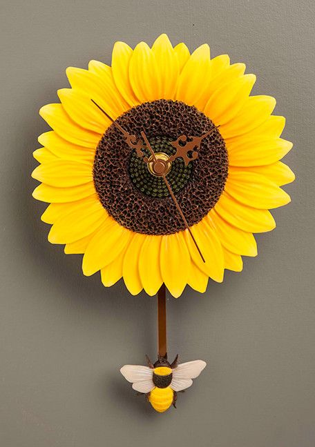 """Beautiful flower blooms transformed into decorative hanging timepieces. Our swinging pendulum clocks are a fun way to keep time with nature! Approximately 6"""" wide X 9.5"""" high. Uses one AA battery, not"""