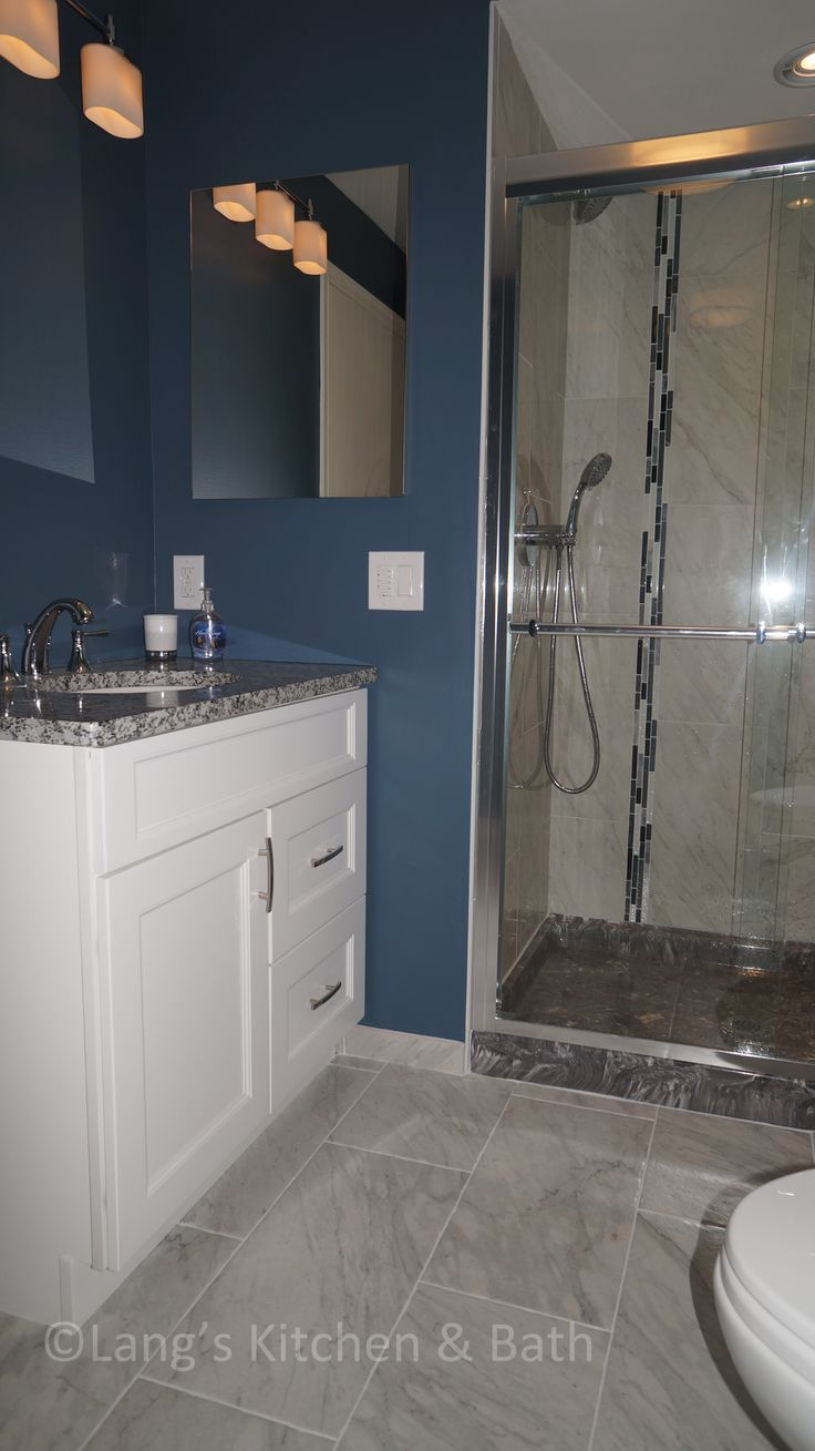 This transitional style bathroom design beautifully contrasts a white Fabuwood vanity cabinet and American Standard tub with the blue wall color.  Gray tile and a mosaic tile design in the shower storage niche pull together the color scheme and create an eye catching design.  The shower is finished off with a Dreamline shower door and a gray shower base.