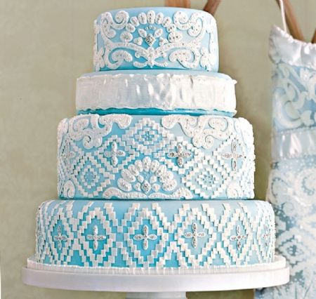 "Lovin Sullivan Stylish Wedding Cakes    Bridal gowns – especially ornately adorned ones – provide an elegant source for lacy layers of icing. To echo the pastel underlay of this Reem Acara stunner, Sullivan covered a four tier cake in pale blue fondant. White royal icing and fondant mimic the embroidery, while silver dragees replicate the beads."" In Style Weddings"