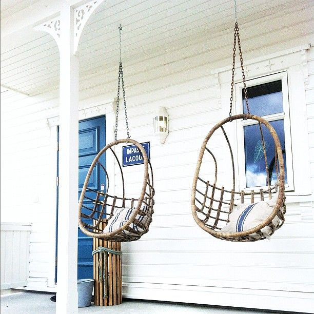 Rattan porch swings + white house