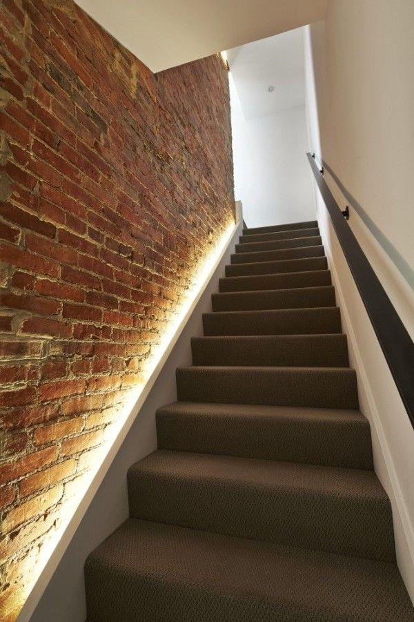 Lighting along the staircase against a brick wall