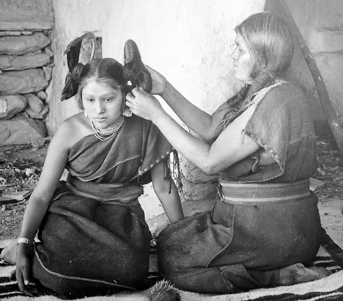 "Hopi woman dressing hair of unmarried girl, 1900. The ""squash blossom"" hairdo indicated eligibility for courtship."