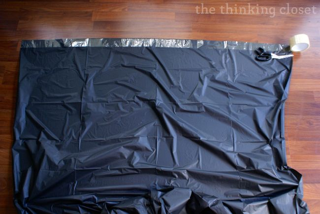 DIY plastic tablecloth backdrop Step 2: Run a strip of clear packing tape across the top of your tablecloth.