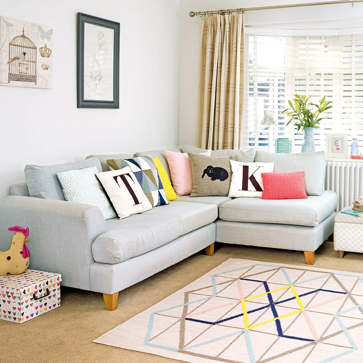 Grey living room with pastel accessories and L-shaped sofa