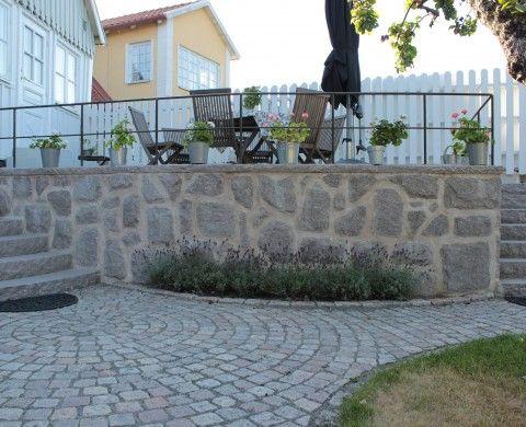 Naturstenen kompletterar det klassiska 1700-talshuset på Österlen. Cirkellagd begagnad gatsten och en mur med kryssmönster av råkilad Grå Bjärlövsgranit