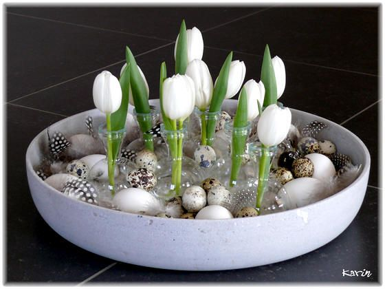Easter flower arrangement with tulips, eggs and feathers in shells sand