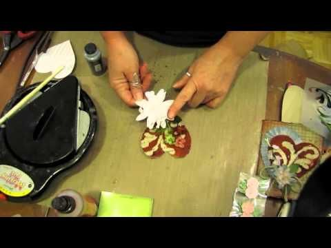Mixed media video including creating a plastic template from a cutting machine, using beeswax in a melting pot for a resist and for dipping decorations to change colour, and placing on a cut out piece of canvas.  Decorations are topped ontop of a card that is distressed and inked.