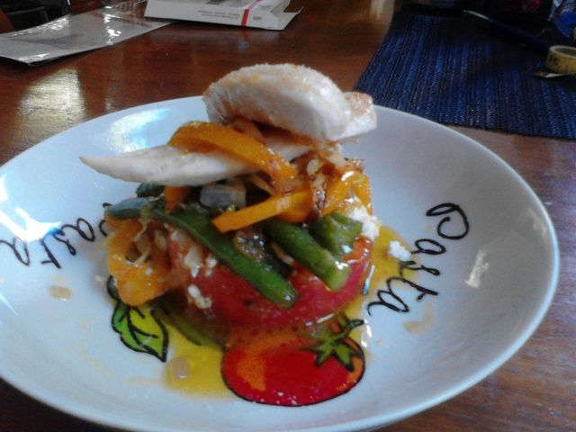 Monk fish stack with green beans, red onion, peppers on a round disk of steamed rice