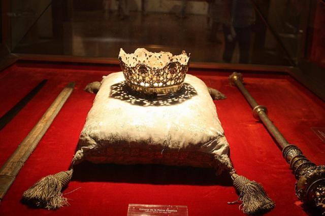 CORONA DE ISABEL LA CATÓLICA La corona de Dª Isabel (14 cm de diámetro) destaca por su gran sencillez; es de plata sobredorada y presenta aro inferior liso y parte superior calada con tallos entrelazados, granadas y hojas.