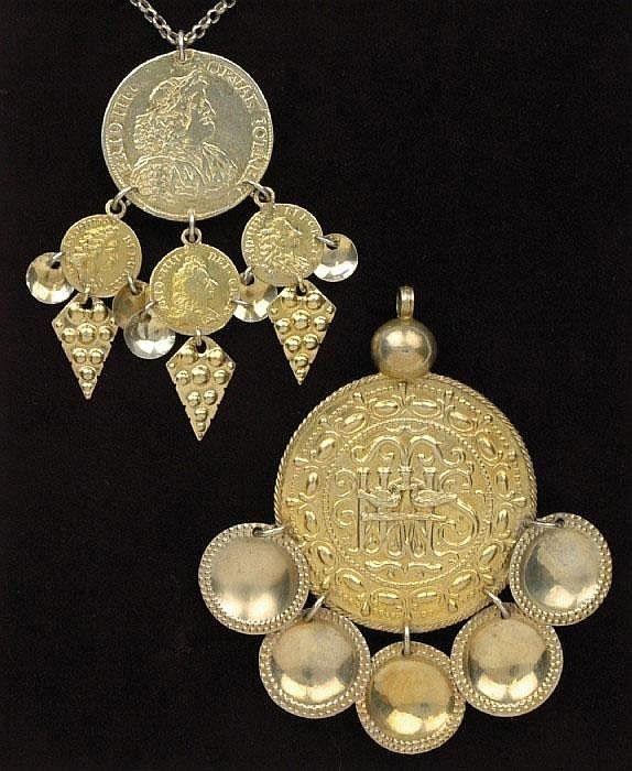 """Traditional silver pendants. """"TRILLEKORS och PENGAKORS, i silver Trillekorset delvis förgyllt med fem skålformade hängen. Dekor med sammanflätat IHS och pålagda parställda fåglar. Penningkorset förgyllt med danskt mynt 1666. Behängt med tre mindre mynt, löv och skålformade hängen."""""""