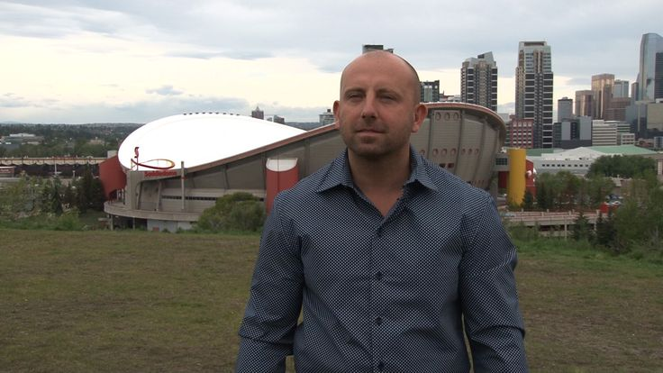Chad Sherger gleaming with pride for his final result of the Saddledome (background)