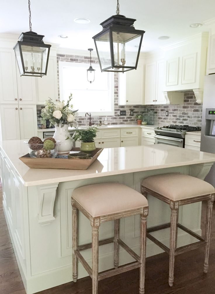 Such a pretty kitchen with some great design for a smaller kitchen.  I like the whitewashed brick backsplash, the detail on the island, pretty lanterns, and how light and bright it is.