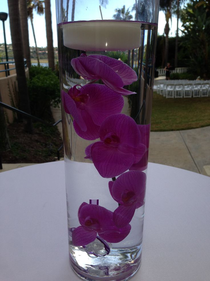 Purple Orchids In A Cylindrical Vase With Candle At The Top Make For Great Centerpiece That Transitions From Daytime To Evening
