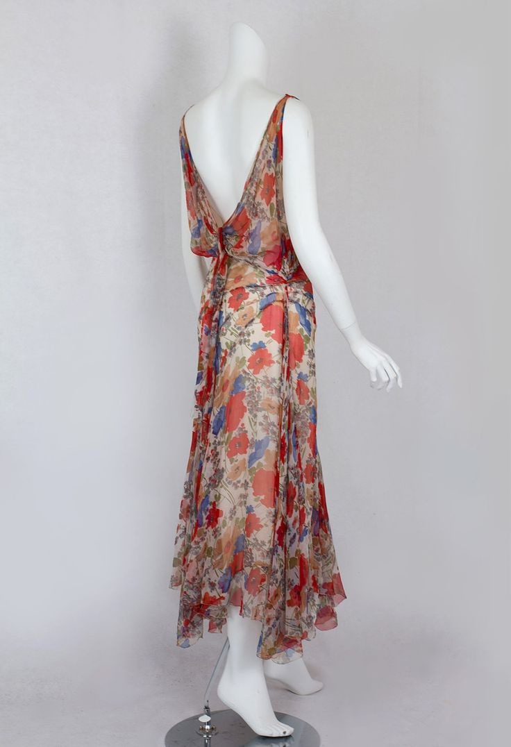 Floral chiffon dress with low cut back, 1930s. This silhouette became synonymous with Hollywood sophistication during the Depression when America craved fantasy and beauty. The bias-cut bodice, dipping almost to the waist in back, is tied with a flirty sash. The skirt is form fitting to the hipline where it takes on an exaggerated sweep with bias-cut panels.