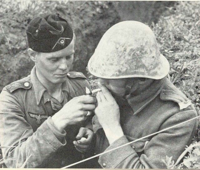 Romanian soldier has a cigarette lit by his German comrade.