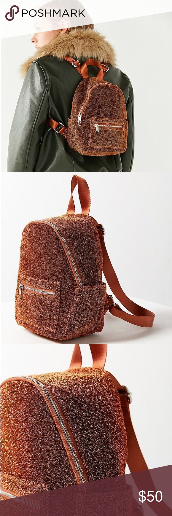 """Glitter classic mini backpack purse rust orange Life's a party so you might as well accessorize accordingly with this glittery mini backpack we're so obsessed with. Kitschy-cute zip-around silhouette with zippered pocket and pouch pockets at sides and front for easy access to your sunglasses + phone. Finished with adjustable shoulder straps and a top carrying handle.  Content + Care - Spot clean   Size - Length: 7.5"""" - Width: 4.5"""" - Height: 10"""" - Handle drop: 4"""" 1.25 Bags"""