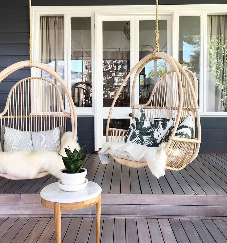 want to spice up your living room with the latest home decor trend? Look no further than a rattan hanging chair! How fun is this outdoor covered patio with these casual and fun hanging chairs?! Make them super comfy by adding a fur throw to the chair