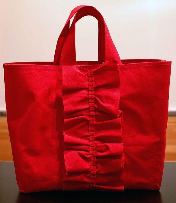 ひらひらフリルでお出かけが楽しくなりそうなトートバッグ。 大きめサイズなのでママバッグとしても活躍しそう。パラフィン加工が施された10号帆布を使用しているので、とても丈夫です。 赤以外にネイビーもございます(写真4枚目を参照ください)✩✩受注生産となります✩✩ご注文いただいてから1週間から10日ほどお時間をいただく場合があります。 発送日の目処をあらかじめお知らせいたします。■SIZE■横(上部)約49cm横(下部)約39cm縦 約37cmマチ 約14cm持ち手 約60cm (ご希望の長さがあればご注文時にお知らせください) 内ポケット 横21cm 縦18cm