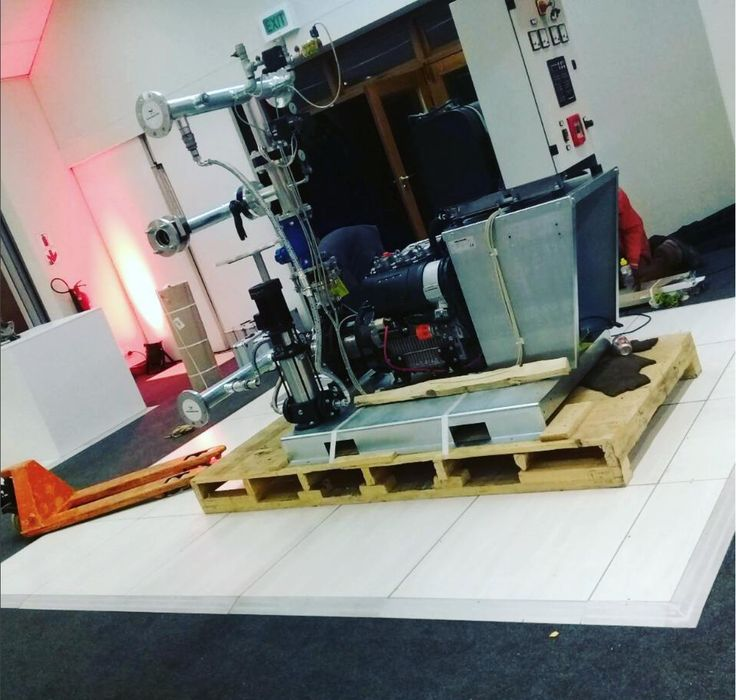 Pearl Teak demonstrating its strength beneath a heavy-looking piece of machinery at an expo #connectafloorcape #eventflooringcape town