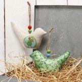 Een stoffen vogel gedecoreerd met decoupage papier en kralen