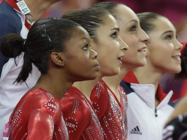 Olympics: Day 4 - U.S. gymnasts, from left to right, Gabrielle Douglas, Alexandra Raisman, Jordyn Wieber and McKayla Maroney watch the screen moments before the results were declared during the Artistic Gymnastic women's team final at the 2012 Summer Olympics, Tuesday, July 31, 2012, in London. Team U.S. won the gold medal. (AP Photo/Julie Jacobson)