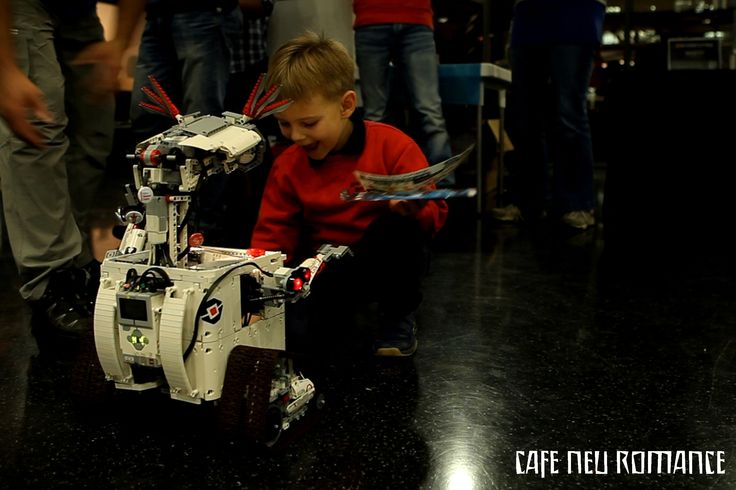 Boy is interacting with a LEGO Wall-E replica at Cafe Neu Romance 2014.  For more information on the Robot Performance Festival Cafe Neu Romance: http://cafe-neu-romance.com/home