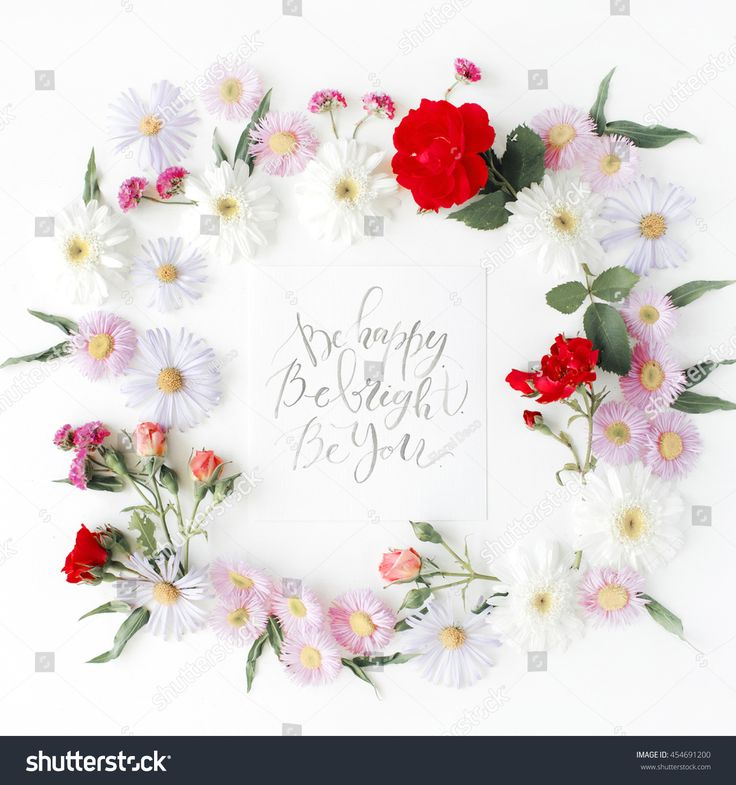 """inspirational quote """"be happy, be bright, be you"""" written in calligraphy style on paper with pink, red roses, chamomiles and leaves isolated on white background. Flat lay, top view"""