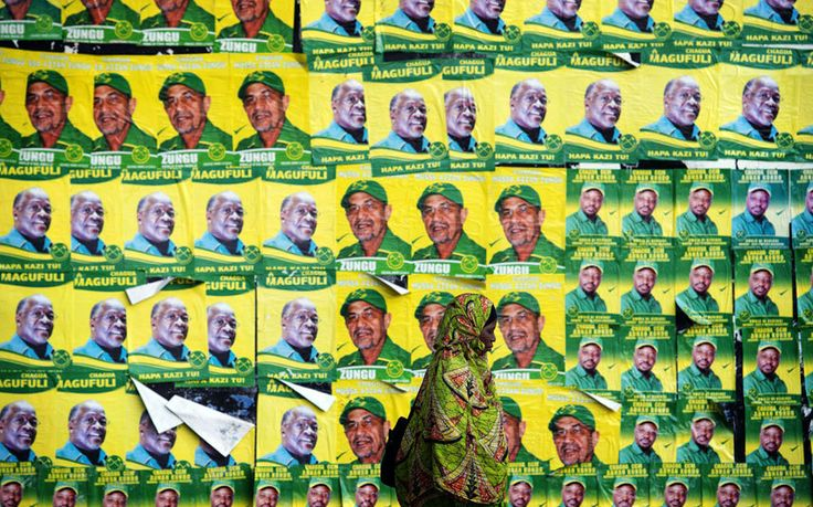 A woman walks past posters for ruling party Chama Cha Mapinduzi (CCM) presidential candidate John Magufuli and parliamentary candidate Hassan Zungu in Dar es Salaam, Tanzania