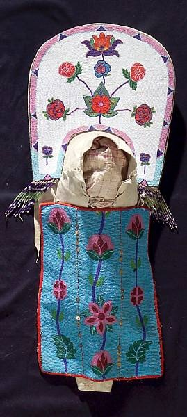 A Nez Perce beaded cradle  •  The wood backboard wrapped in hide, with floral design beaded across the top and beaded fringe alongside the head opening, a fully-beaded panel of flowering vines draped across the front.  length 36in