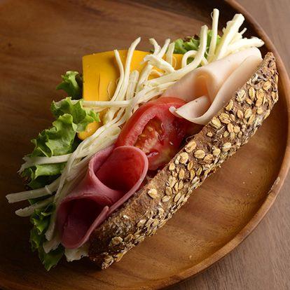 Kepekli Ciabata Ekmeğine Karışık Sandviç Jambon çeşitleri, cheddar peyniri, dil peyniri ve marul bulunmaktadır.