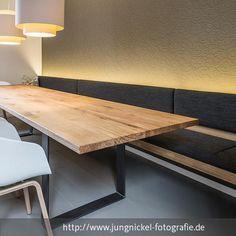Zeigt den großen Holztisch im Esszimmer, die Bestuhlung und die Deckenbeleuchtung