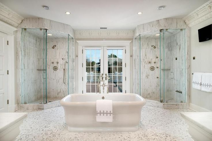 Luxurious bathroom features corner his and her showers clad in gray and white marble lined with a corner shower caddy flanking a freestanding tub and floor mount tub filler, placed dead center of the room, atop a mosaic marble grid tiled floor placed in front of French doors.