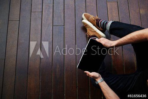 Male student using touchpad while sitting on wooden floor