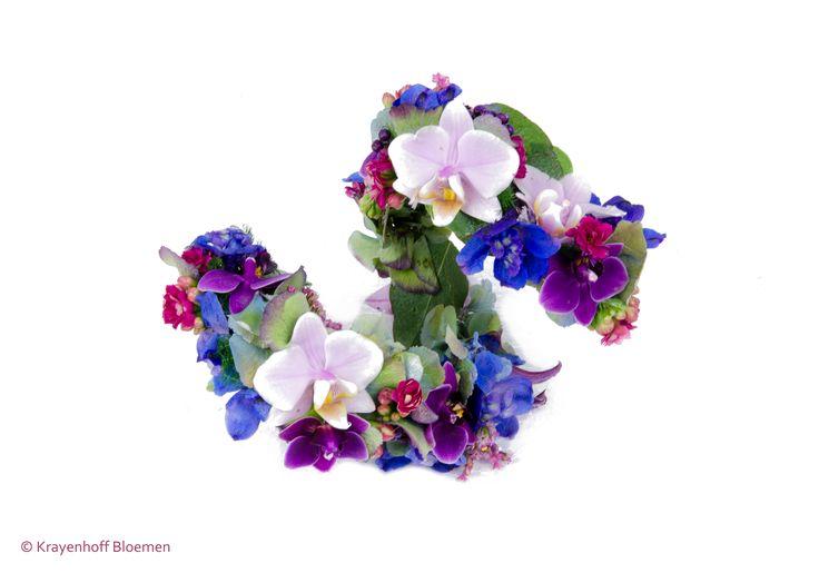 Polscorsage voor een bruid gemaakt op ijzerdraad van verfijnde bloemen in de kleuren roze, paars en blauw.