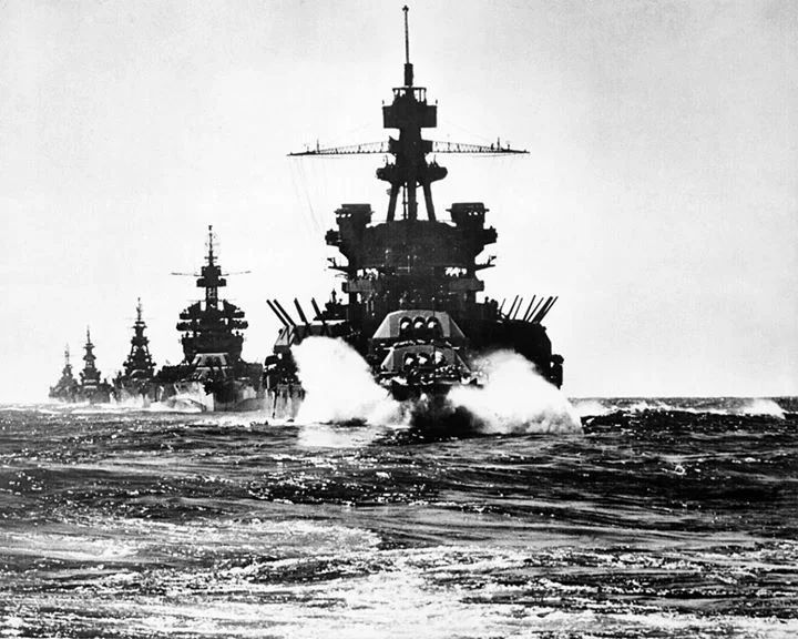 "Photo:  USS PENNSYLVANIA and battleship of COLORADO classfollowed by three cruisers move in line into Lingayen Gulf preceding the landing on Luzon."" Philippines, January 1945."