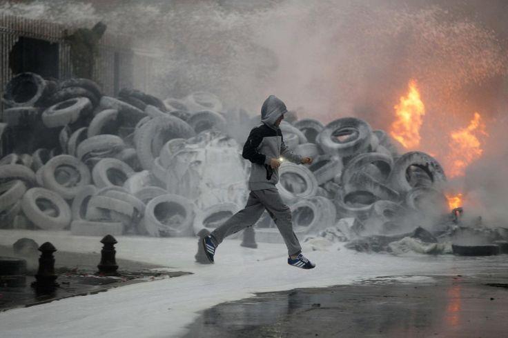 19.08 Au nord-ouest de la France, un homme passe devant une pile de pneus en feu alors que les fermiers de la région protestent devant la préfecture.Photo: Charly Triballeau